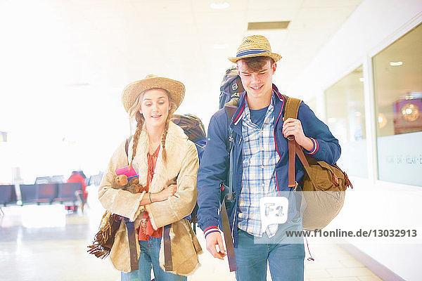 Junges Paar am Flughafen  Rucksäcke tragend  auf dem Weg zur Reise