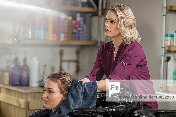 Friseur trocknet Kundenhaare im Salon