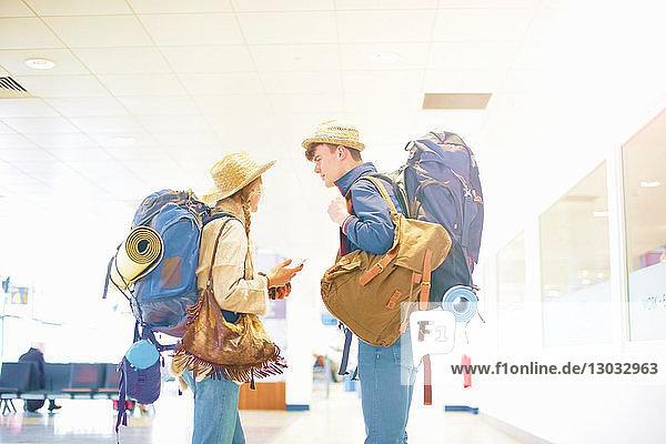 Junges Paar am Flughafen  Rucksäcke tragend  von Angesicht zu Angesicht stehend  redend