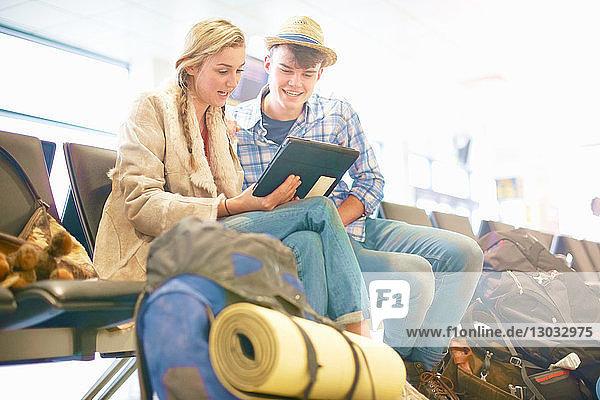 Junges Paar am Flughafen  sitzend  von Rucksäcken umgeben  mit digitalem Tablett  niedriger Blickwinkel