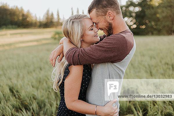 Romantischer Mann und Freundin umarmen sich im Feld aus langem Gras