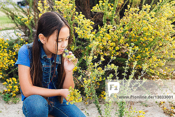 Girl kneeling to smell plant