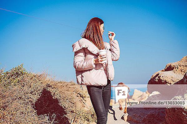 Mittlere erwachsene Frau am Strand beim Spaziergang mit ihrem Hund  Odessa  Odeska Oblast  Ukraine