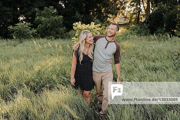 Romantische junge Frau und ihr Freund beim Spaziergang im langen Grasfeld