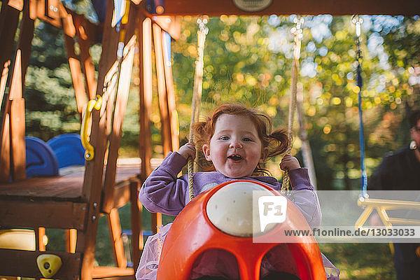 Mädchen mit roten Haaren auf Spielplatzschaukel schwingend  Portrait