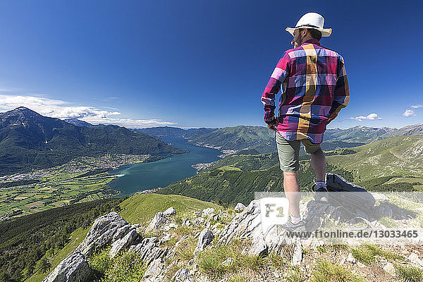 Hiker on top of Monte Berlinghera looks towards Colico and Monte Legnone  Sondrio province  Lombardy  Italy