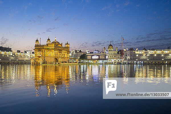 The Golden Temple (Harmandir Sahib) and Amrit Sarovar (Pool of Nectar) (Lake of Nectar)  illuminated at dusk  Amritsar  Punjab  India
