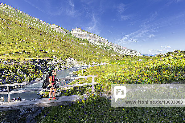 Woman hiker runs across a footbridge  Unterer Segnesboden  Flims  District of Imboden  Canton of Grisons (Graubunden)  Switzerland