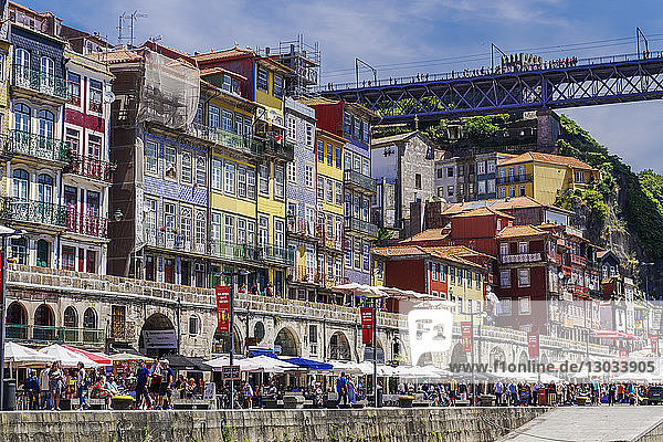 Traditional colourful buildings with balconies and umbrellas on the bank of Douro River in the Ribeira District  Porto  Portugal