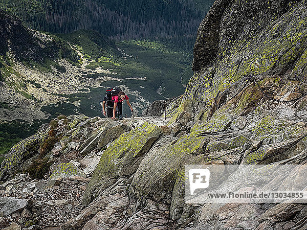 Lady scrambling on Swinica  2301m  using metal chains  on the Polish and Slovak border in the Tatra Mountains  Poland