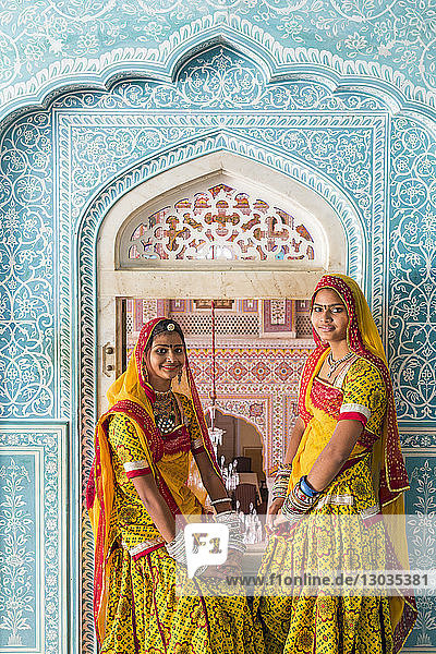 Ladies wearing colourful saris in ornate passageway  Samode Palace  Jaipur  Rajasthan  India