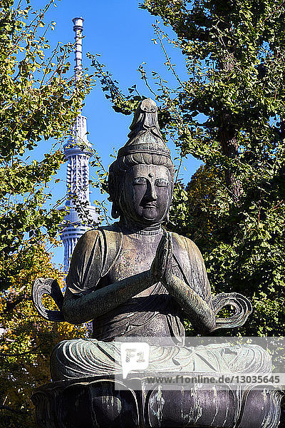 Kannon Bosatsu Buddha sculpture at the Sensoji Temple with the Sky Tree Tower in the background  Asakusa  Tokyo  Japan