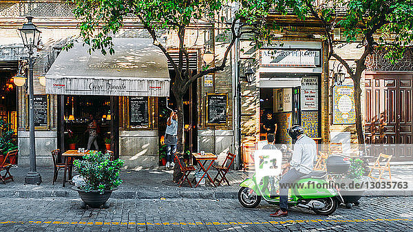 Man on green Vespa on Calle Mateos Gago in the historic centre of Seville  Andalusia  Spain