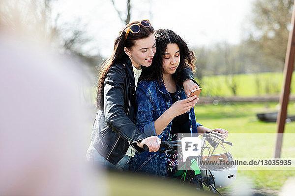 Teenager-Mädchen lesen gemeinsam Texte auf dem Fahrrad