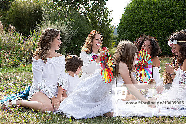 Female friends and family having picnic in garden