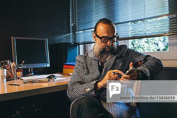 Man using cellphone at desk