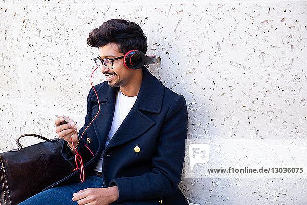 Geschäftsmann hört MP3 mit Kopfhörern