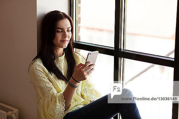 Teenagerin liest Textnachricht auf Handy durch Glasfenster