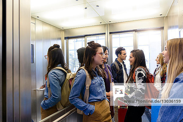 University students talking inside elevator