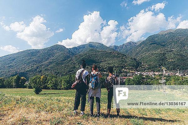 Drei junge Wanderfreunde mit Blick auf die Berge  Rückansicht  Primaluna  Trentino-Südtirol  Italien