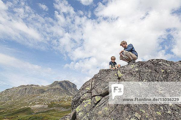 Junge und Vater kauern auf einer Felsformation  Blick aus niedrigem Winkel  Oppland  Nord-Trondelag  Norwegen