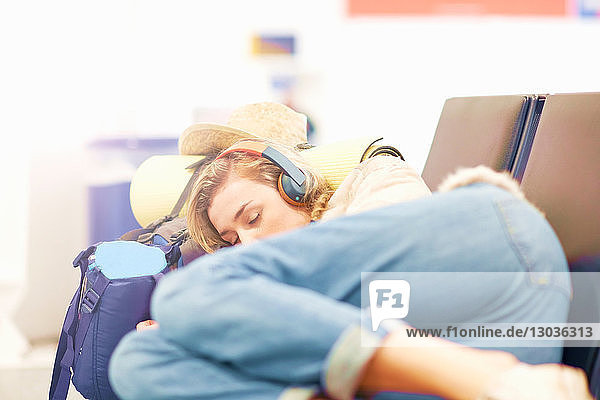 Young woman at airport  sleeping on seating in departure lounge