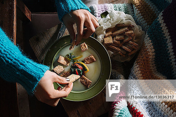 Young woman placing savoury biscuits in bowl of fresh food