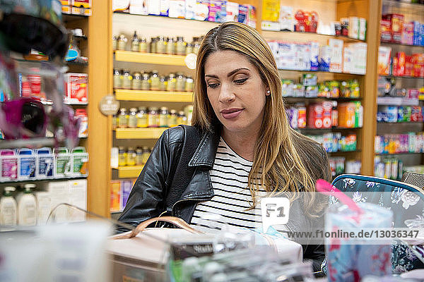 Pregnant mid adult woman looking at medicine and health products in pharmacy
