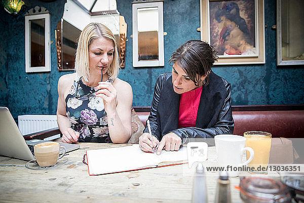 Frauen beim Brainstorming von Geschäftsideen im Restaurant