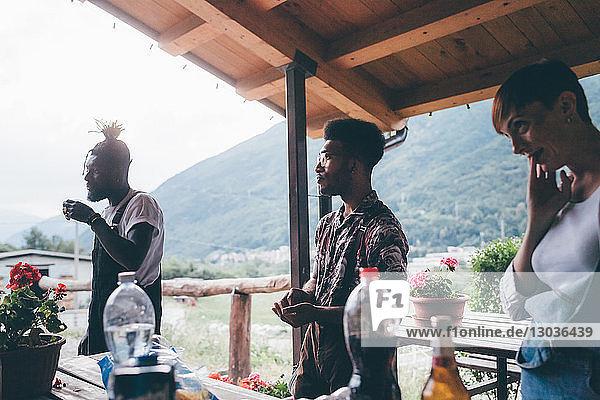 Drei junge erwachsene Freunde machen eine Pause auf einer ländlichen Veranda