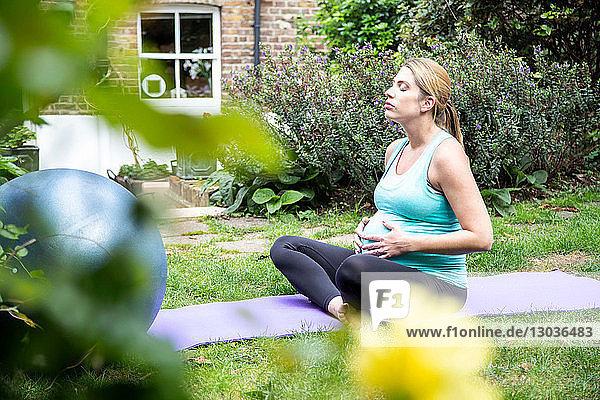Schwangere Frau im mittleren Erwachsenenalter praktiziert Yoga-Meditation im Garten