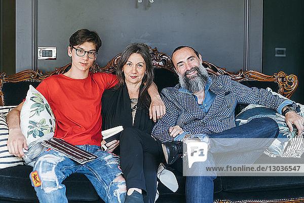 Auf antikem Sofa sitzendes Ehepaar mit Sohn