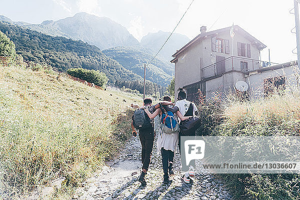 Junge erwachsene Wanderfreunde mit den Armen umeinander auf der Landstraße  Primaluna  Trentino-Südtirol  Italien