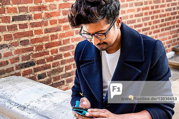 Geschäftsmann mit Smartphone vor dem Gebäude