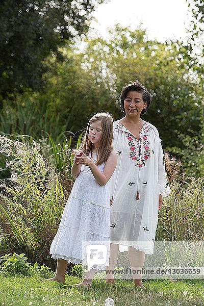 Frau und Mädchen genießen Garten
