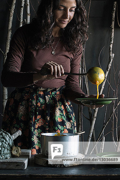 Young woman ladling fresh soup from saucepan at rustic kitchen counter