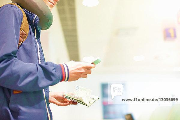 Junger Mann am Flughafen  mit Smartphone  Pass in der Hand  Mittelteil  niedriger Blickwinkel