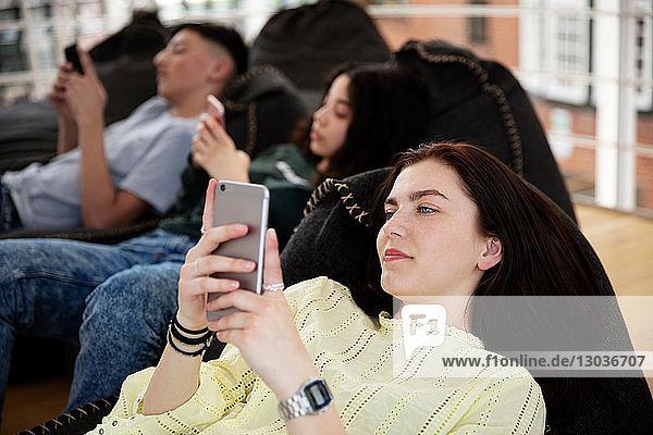 Schulfreunde liegen auf Sitzsäcken und schreiben in der Schule SMS