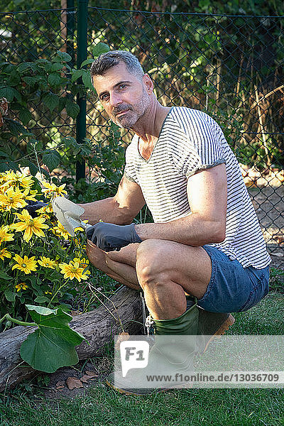 Man with trowel by flower bed