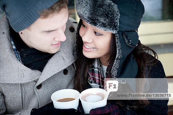 Junges Paar mit Winterhüten und Getränken zum Mitnehmen