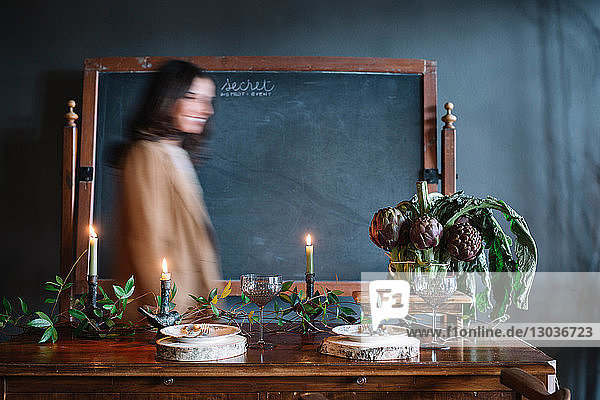 Young woman moving past vintage dinner table with candles and bowl of globe artichokes