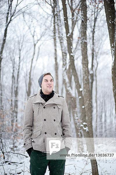 Junger Mann steht in schneebedecktem Wald  Ontario  Kanada