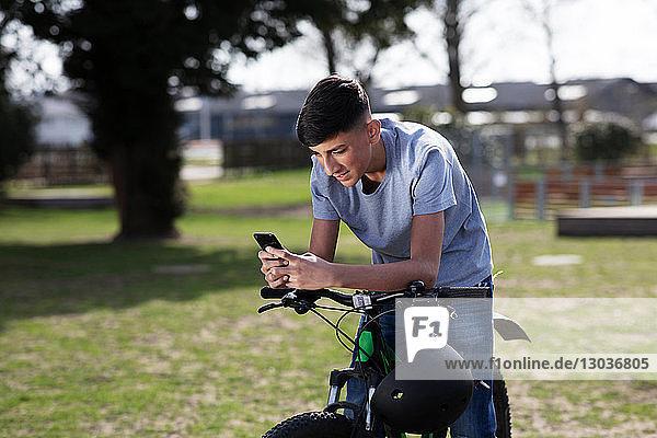 Teenager-Junge schreibt SMS auf dem Fahrrad