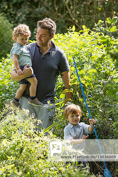 Vater und Kinder gehen im Park spazieren