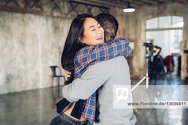 Couple hugging in open plan studio