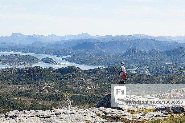 Boy and father looking out at inlet landscape from rock formation  Aure  More og Romsdal  Norway
