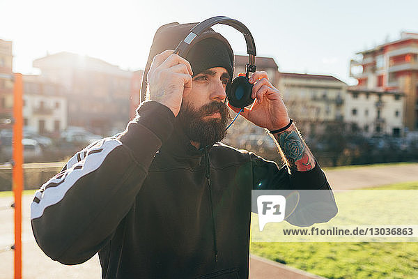 Man in hoodie using headphones