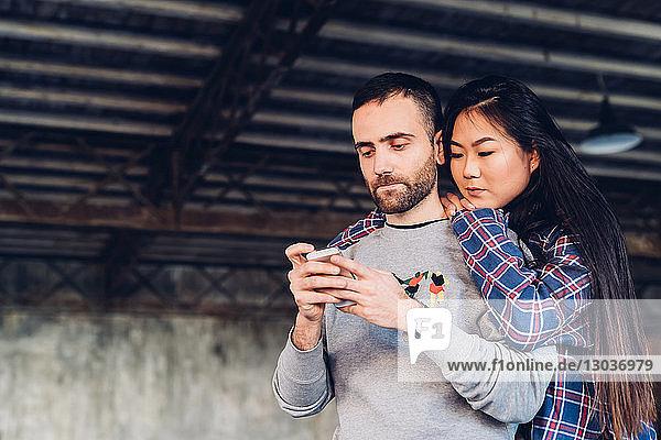 Frau schaut einem Mann beim Benutzen eines Smartphones über die Schulter
