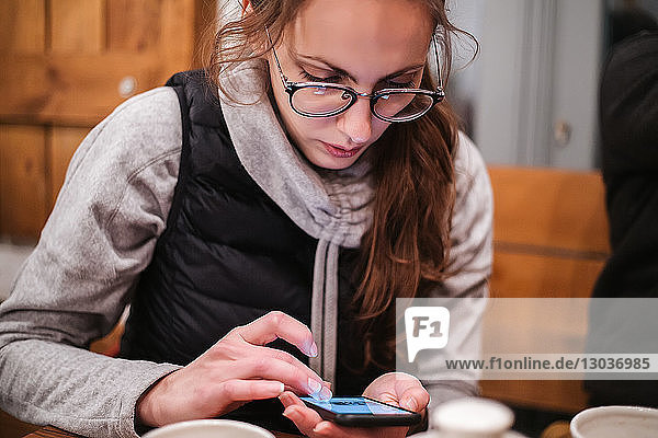 Junge Frau benutzt Smartphone im Café