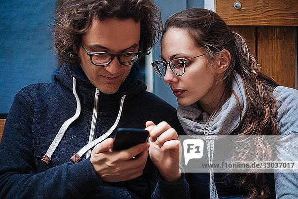 Mittelgroßer erwachsener Mann und Freundin schauen auf Smartphone